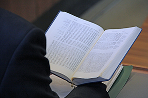 A student holds open a book while studying in class.