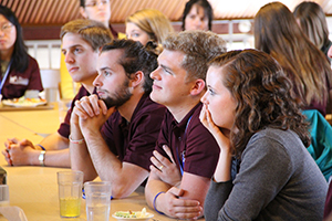 Prospective students focus on a speaker off-screen during Christ Academy College and Phoebe Academy College.