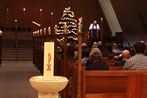The Christ candle sits in the foreground while in the background a pastor preaches an Advent sermon.
