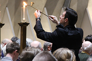 Seminarian Daniel Schuetz lights the candles in Kramer Chapel for All Saints' Choral Vespers.